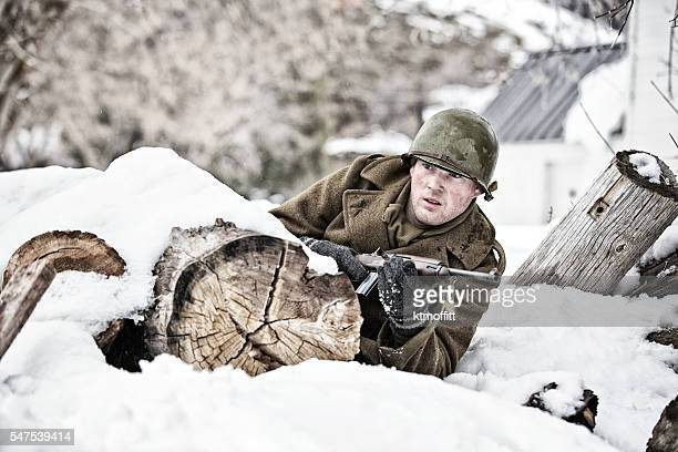 Young WWII GI Rolling for Shelter Behind Snow Covered Log