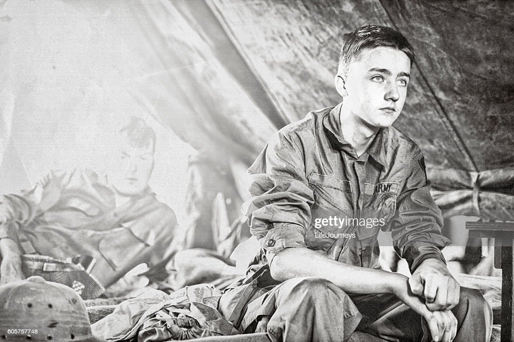 Young WWII Infantryman Sitting On A Cot In His Tent : Stock Photo