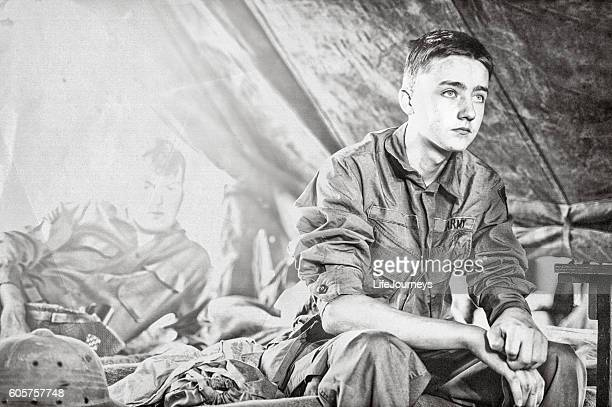 young wwii infantryman sitting on a cot in his tent - world war ii stock pictures, royalty-free photos & images