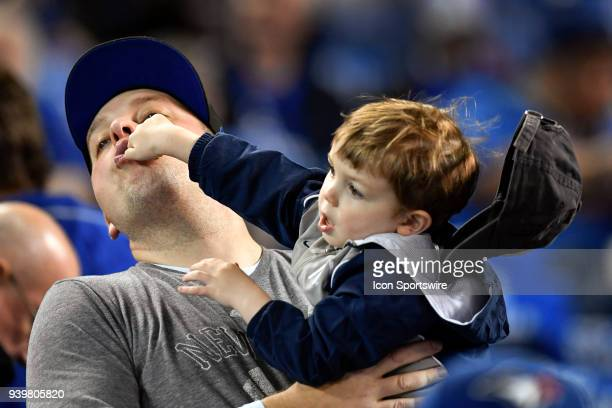 A young Yankees fan play hits his dad in the face and loses his hat before the MLB seasonopener game between the New York Yankees and the Toronto...