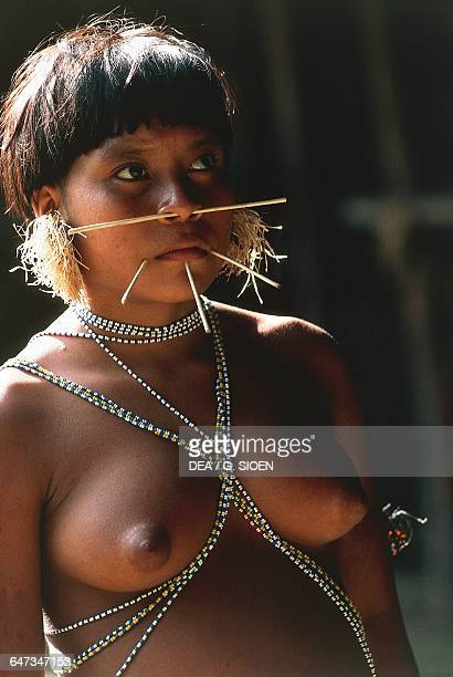 Young Yanomami woman with fine palm sticks through her face traditional symbols of beauty The Amazon rainforest Venezuela