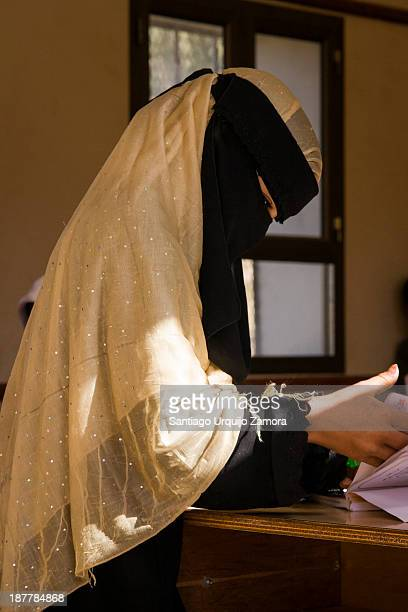 Young Yemeni girl wrapped with a yellow and black abaya studying at a rural school in Argesh, Haraz Mountains, Yemen. The Yemeni government says the...