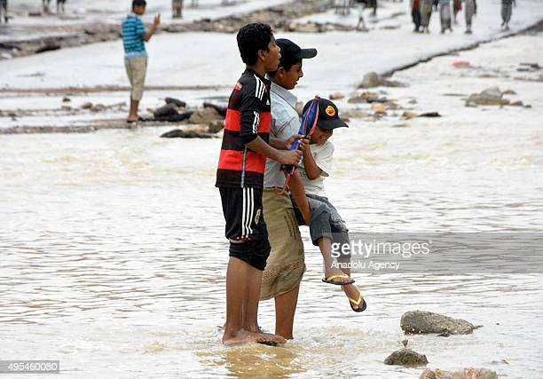 Young Yemenis walk through wind and heavy raincaused floodwaters as a result of Cyclone Chapala generated in the Arabian Sea on the shore of...