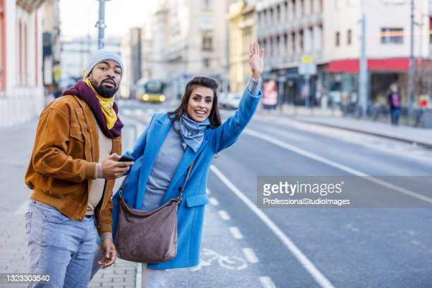 young young multi-ethnic couple is standing in the street and waving with arm to catch a taxi. - world sports championship stock pictures, royalty-free photos & images