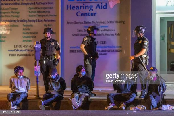 Young young sit in handcuffs under arrest during an emergency curfew during demonstrations following the death of George Floyd on May 31 2020 Santa...