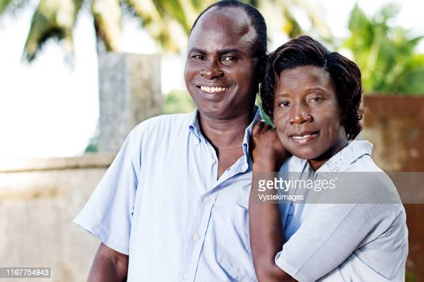 young young woman runs her husband by putting her hands on his  shoulder. - femme ivoirienne photos et images de collection