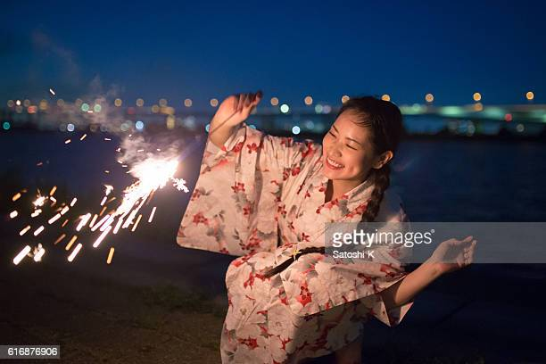 Young yukata woman playing sparker nearby river