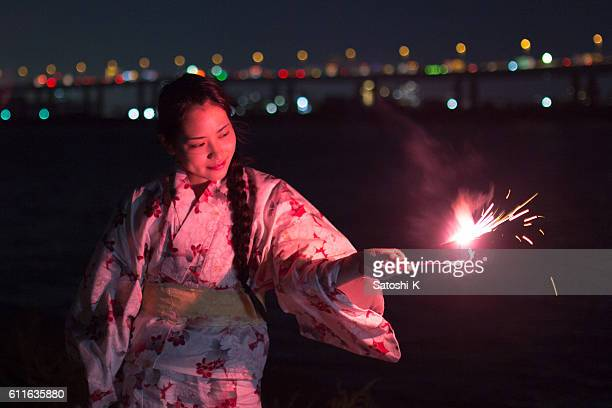 Young Yukata woman playing sparkler nearby river