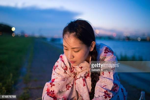 Young yukata woman sitting nearby river