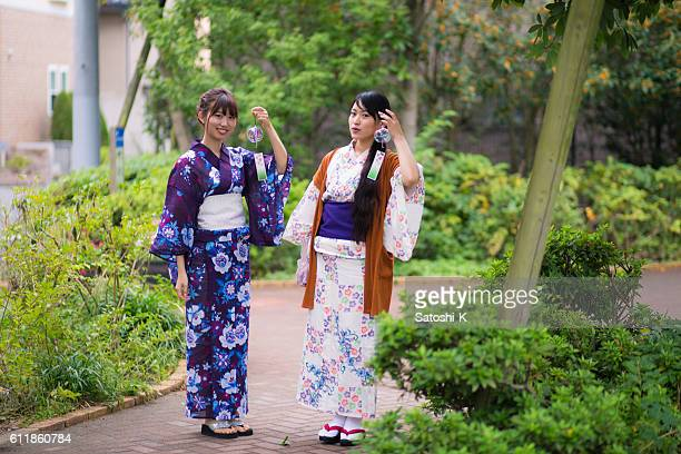 Young yukata women walking in green park with wind bells