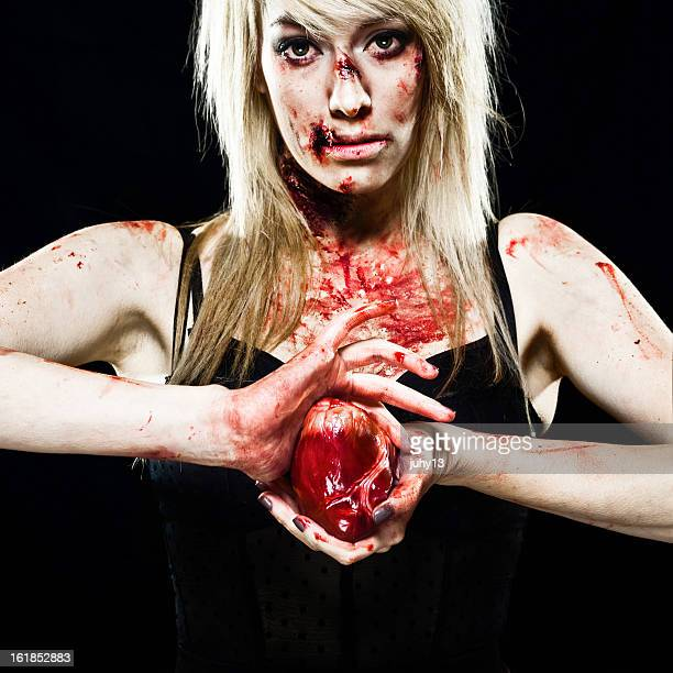 young zombie girl with a human heart - bloody heart stockfoto's en -beelden