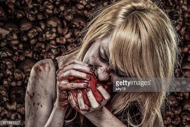 young zombie woman eating a human heart - bloody heart stock photos and pictures
