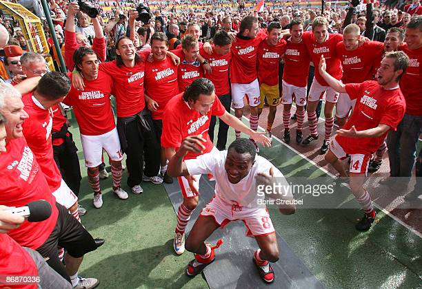 Younga-Mouhani , Kenan Sahin and Sebastian Boenig dance in the center of their team mates of 1.FC Union Berlin, who celebrates the ascension to the...