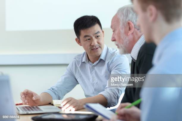 Younger and older scientists discussing pharmaceutical science project in meeting room