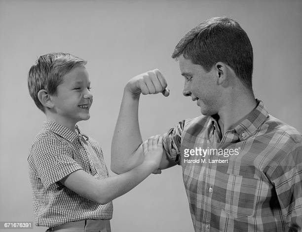 Younger Brother Touching Biceps Of Elder Brother