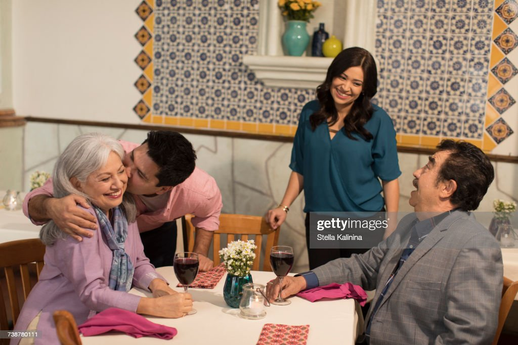 Younger couple greeting older couple in restaurant : Stock Photo