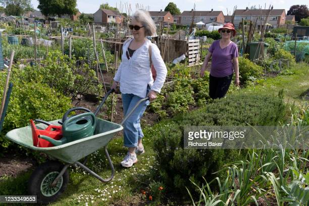 Younger woman pushes full watering cans in front of her elderly mother at the family vegetable allotment plot, on 30th May 2021, in Nailsea, North...