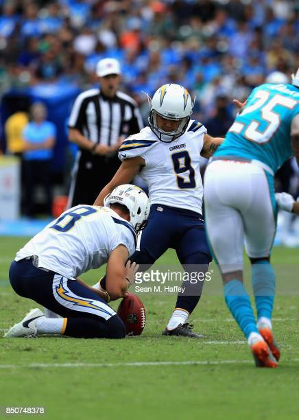Younghoe Koo kicks a fieldgoal as Drew Kaser of the Los Angeles Chargers holds during the second half of a game against the Miami Dolphins at StubHub...