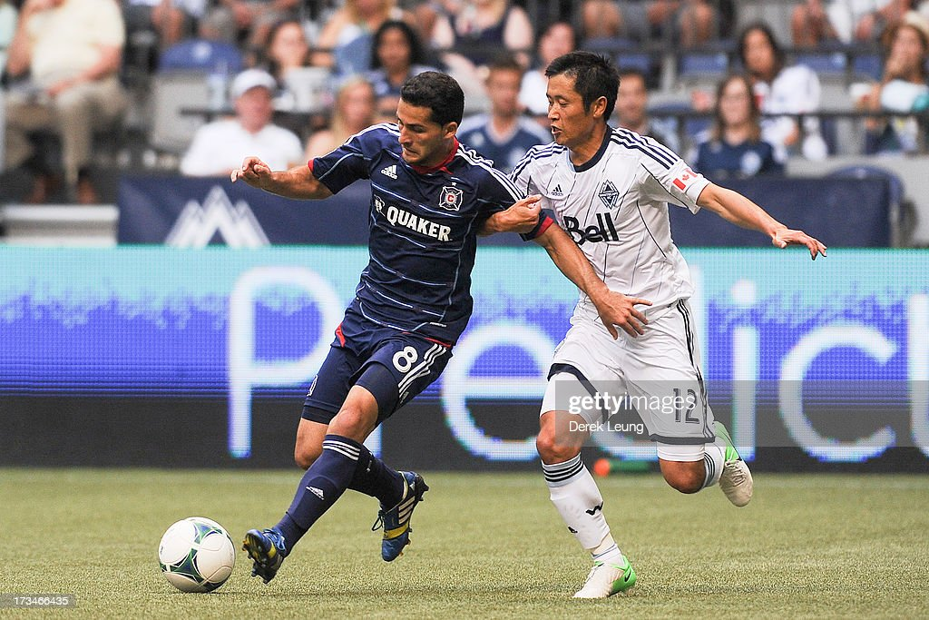 Young-Pyo Lee #12 of the Vancouver Whitecaps tries to check Dilly Duka #8 of Chicago Fire during an MLS Match at B.C. Place on July 14, 2013 in Vancouver, British Columbia, Canada. The Vancouver Whitecaps won 3-1.