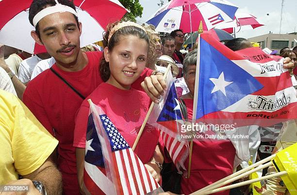 Youngster carries American and Puerto Rican flags at a ceremony outside the Captiol Building in San Juan marking the 50th anniversary of the Puerto...