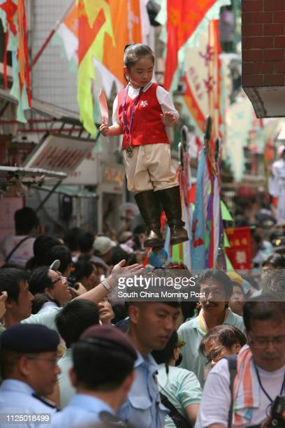 Youngster dresses as mythological figures and held aloft on hidden rods appears to float above the heads of the crowd at The annual Cheung Chau Bun...
