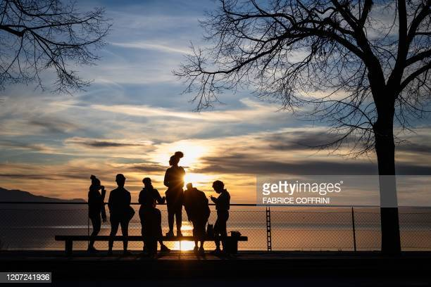 TOPSHOT Youngster gather at sunset above Montreux on March 15 2020 Swiss officials urged people not to be afraid as cases of COVID19 surged and...