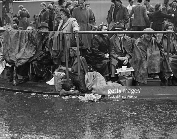 A youngster in the Mall lying down through the rain on the evening before the Coronation London 1st June 1953