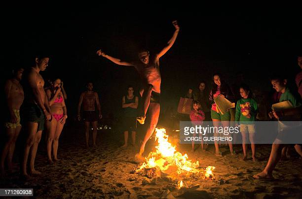 A youngster jumps over a bonfire early on June 24 during the traditional San Juan's night in a beach of Malaga southern Spain Fires are lit...