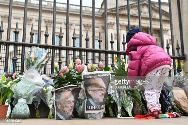Youngster lays a floral tribute at the gates of Buckingham Palace in central London on April 9, 2021 after the announcement of the death of Britain's...