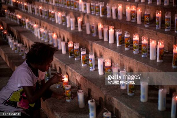TOPSHOT A youngster lights a candle during a protest to mark the 600 days of Brazilian murdered councilwoman Marielle Franco's murder in Rio de...