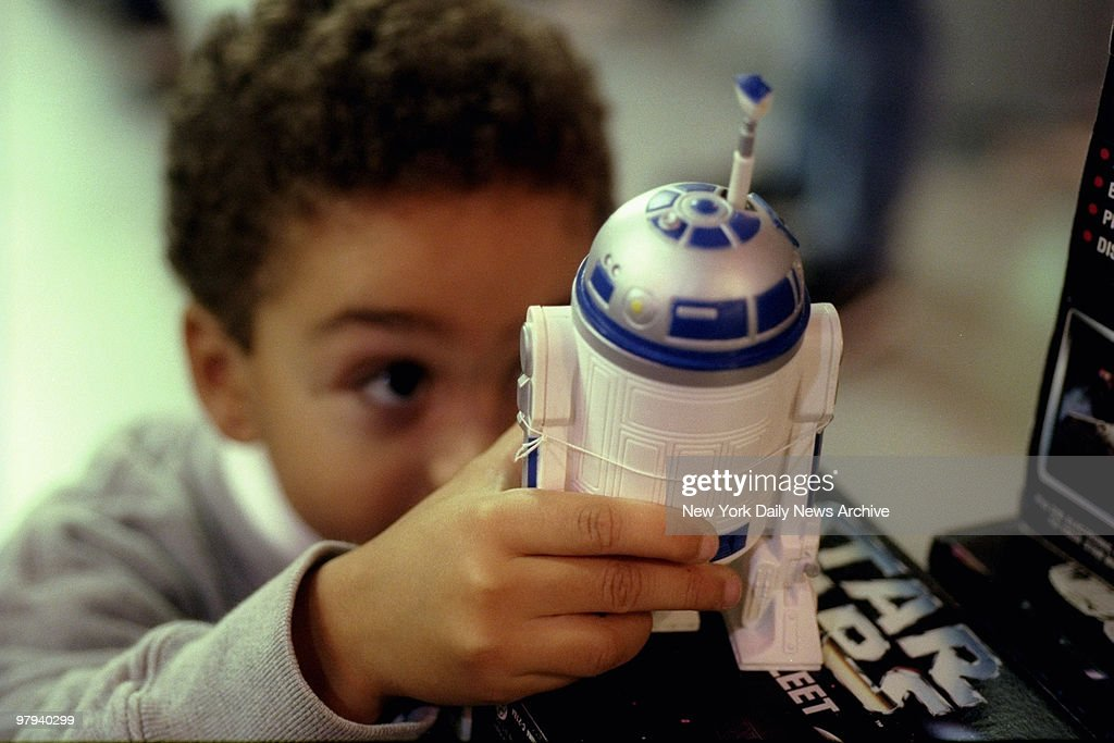 Youngster looks over Star Wars figure R2D2 at F.A.O. Schwarz : News Photo