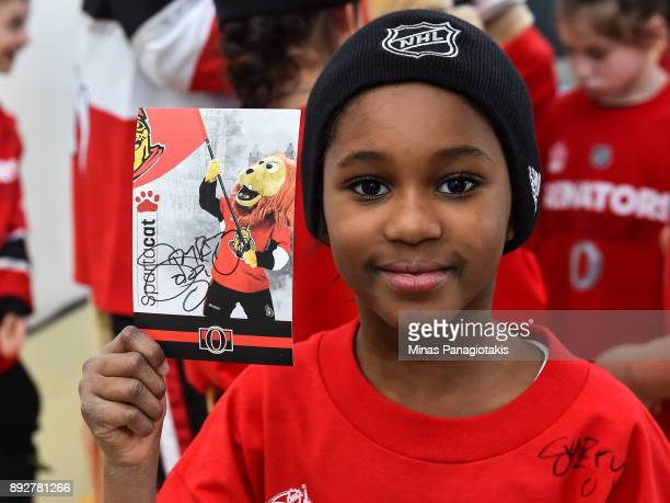 A youngster shows off a signed Spartacat card during the 2017 Scotiabank NHL100 Classic Legacy Project press conference at the Boys Girls Club Police...