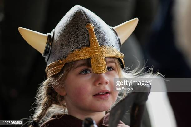 A youngster wears a Viking helmet as other Viking reenactors prepare to march through York during a living history display as part of the 36th York...