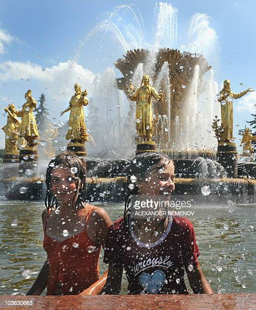 Youngsters enjoy cold water in the Soviet era Fountain of the Nations' Friendship at AllRussian Exhibition Center in Moscow on July 7 2010 The...