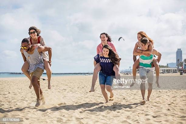 Youngsters giving piggyback ride to friends on beach