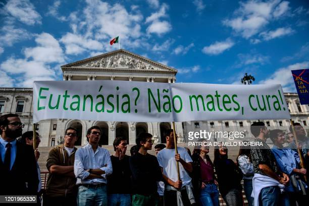 """Youngsters hold a banner reading """"Euthanasia? Don't Kill, cure!"""" during a protest against the decriminalization of euthanasia in front of the..."""