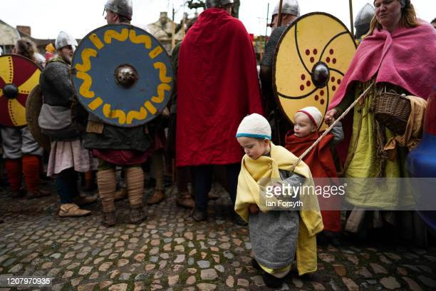 Youngsters in period costume walk past a line of Viking reenactors as they prepare to march through York during the 36th York Viking Festival on...
