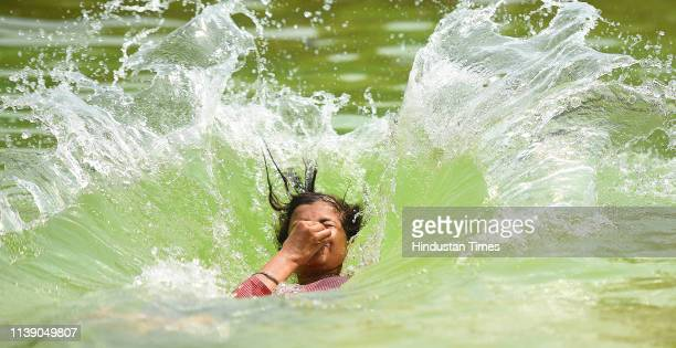 Youngsters play in water on a hot summer day in a pond at Rajpath on April 24 2019 in New Delhi India Delhis Ridge Observatory recorded highest...