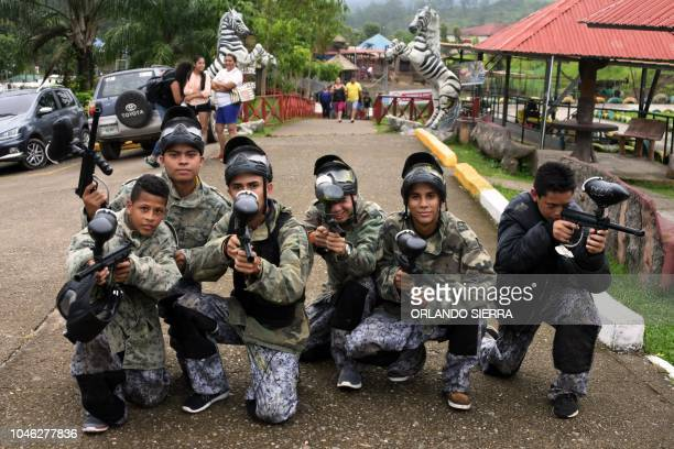 Youngsters pose as they prepare to play paintball at the Joya Grande zoo and ecopark in Santa Cruz de Yojoa Cortes department 160 km north of...