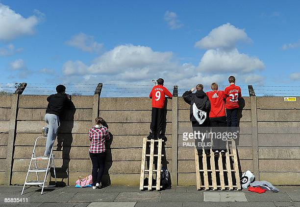 Youngsters scale a wall in order to watch the Liverpool football squad during a team training session at their Melwood training ground in Liverpool...