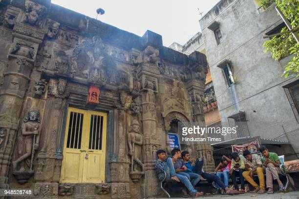 Youngsters sit beside Trishund Ganpati Temple in Somwar Peth construction of this temple was started on 26th August 1754 CE by a person called as...