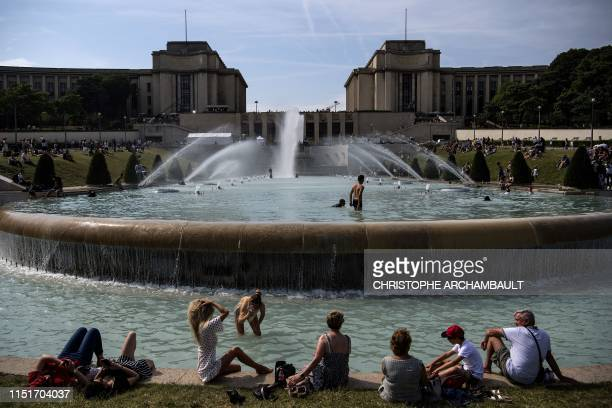 Youngsters sunbathe and cool themselves down in a pond at the Trocadero esplanade in Paris on June 24 as temperatures soar to 33 degrees Celsius. -...