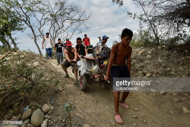TOPSHOT Youngsters transport scrap in a wheelbarrow along an illegal trail from San Antonio Venezuela to Cucuta Colombia on February 27 2019 The...