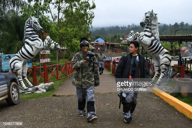 Youngsters walk as they prepare to play plaintball at the Joya Grande zoo and ecopark in Santa Cruz de Yojoa Cortes department 160 km north of...