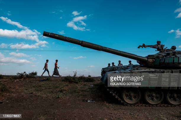 Youngsters walk next to an abandoned tank belonging to Tigrayan forces south of the town of Mehoni, Ethiopia, on December 11, 2020. The town of...