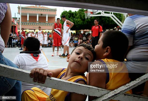 Youngsters wearing Los Angeles Lakers uniforms crowd under the bleachers to watch semi–pro basketball teams play in a tournament during the annual...