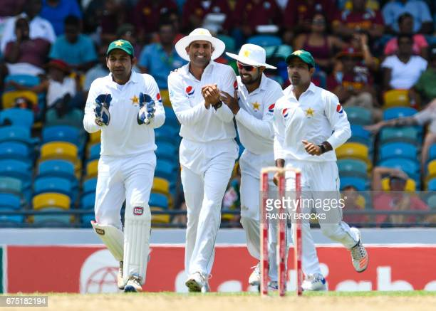 Younis Khan of Pakistan celebrate with Sarfraz Ahmed Babar Azam and Asad Shafiq the catch to dismiss Vishal Singh of West Indies during the 1st day...