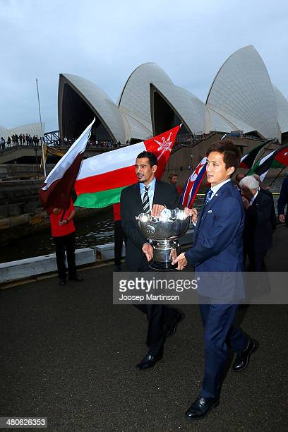 Younis Mahmoud from Iraq and Takashi Fukunishi from Japan carry the AFC Asian Cup trophy ahead of the 2015 AFC Asian Cup draw at Sydney Opera House...