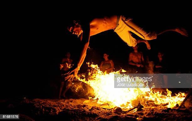 A younth jumps over a bonfire early on June 24 during the traditional San Juan night on a beach in the southern Spanish city of Malaga Fires are lit...