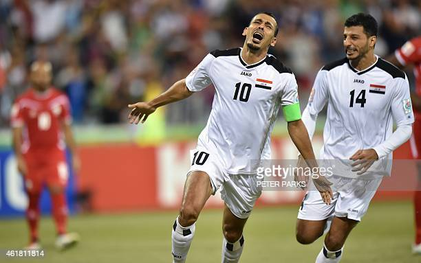 Younus Mahmood of Iraq celebrates scoring the first goal with teammate Salam Shakir against Palestine during their Group D football match of the AFC...